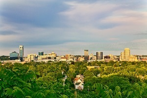 long view of Grand Rapids, Michigan, skyline, with a green forested area in the foreground
