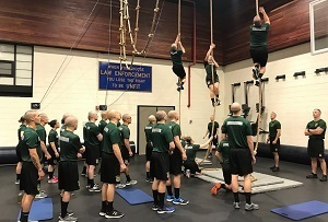 Recruits in the DNR conservation officer academy watch as three fellow recruits climb ropes during physical training