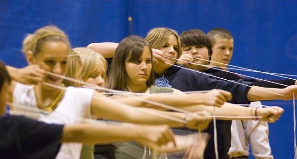 A row of boys and girls using rope to practice lining up their archery shots