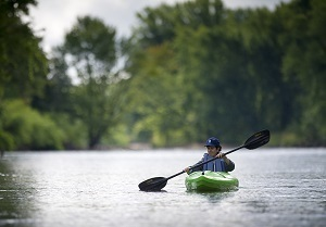 Woman wearing a baseball cap, kayaking on a Michigan river
