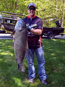 angler poses with state record black buffalo fish