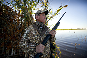waterfowl hunter holding firearm