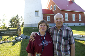 couple that volunteers as keepers stands in front of Tawas Point Lighthouse