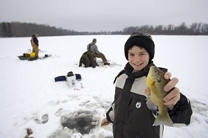 Little boy dressed in winter gear, holding a panfish