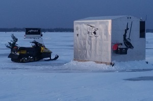 snowmobile and fishing shanty on a frozen lake