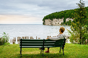 lady on bench overlooking Snail Shell Harbor at Fayette Historic State Park