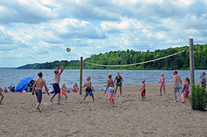 Family playing volleyball on beach at Van Riper State Park