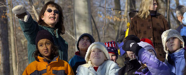 park interpreter leading kids on a winter hike at a state park