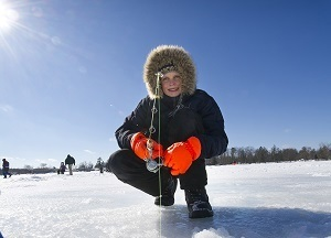 little boy bundled up in winter clothing, holding a fishing pole, on frozen lake