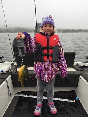 little girl dressed in winter gear on a boat, holding a pumpkinseed fish