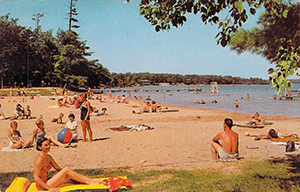 A postcard image from the past depicts beachgoers at Interlochen State Park.