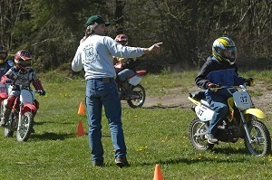 An adult ORV safety instructor guides young riders through a cone course