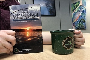 hands holding a Michigan DNR fishing guide and a green DNR coffee mug
