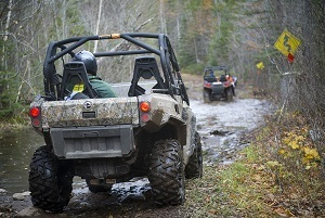 Rear view of an ORV on a muddy trail, with another ORV up ahead