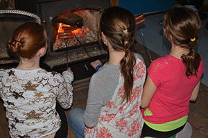 Three young ladies cook their hot dogs over the woodstove fire while winter cabin camping at Van Riper State Park.
