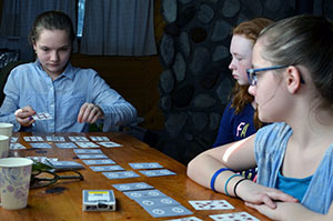 Campers engage in a card game inside the cabin on a March afternoon.
