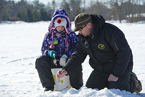 Kori Draper, 7, is given instruction by Ed Shaw, a Michigan DNR interpreter teaching at a Hard Water School fishing clinic.