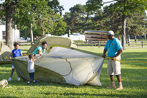 An instructor helps students at an Introduction to Camping event at Belle Isle.