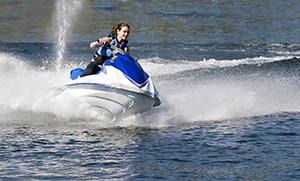 young lady operating jet ski on lake, wearing life jacket