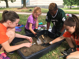 Four children dig in a large bin of dirt during Dig Camp