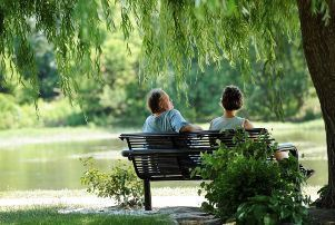 Back view of a man and woman sitting on a bench along the recently restored River Raisin