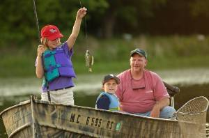 Little girl holding up a fish she caught, standing up in a boat, with a little boy and a man