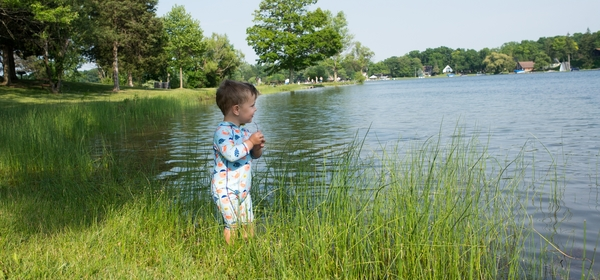 A child stands on a natural lakeshore
