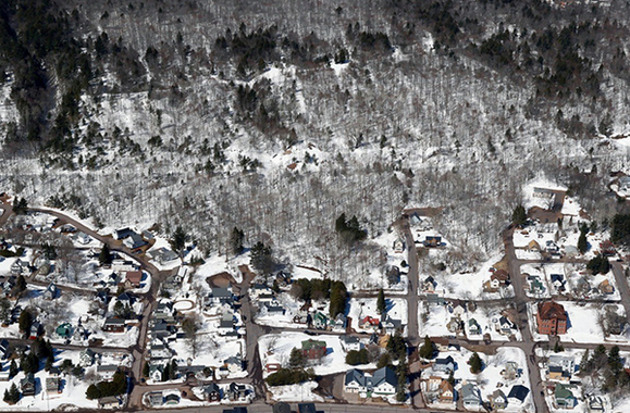 An aerial photo shows an old railroad grade, now a recreational trail, running across the base of a slope above Hubbell in Houghton County.