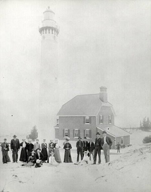 Black and white photo, people on beach in front of Au Sable Point Lighthouse, c. 1905