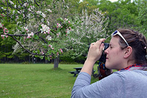 A photography student at a summer Becoming and Outdoors Woman session takes aim at some apple blossoms.