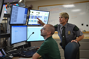 Dispatcher and conservation officer look at monitors in Report All Poaching room