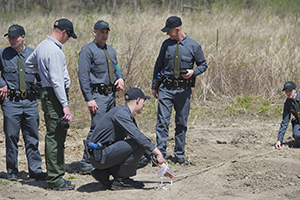 conservation officer recruits measure tire tracks
