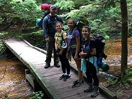 man and girls hiking with backpacks near stream through forest