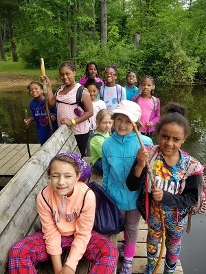 About a dozen Girl Scouts dressed in spring clothing pose on a bridge along a stretch of the Iron Belle Trail.