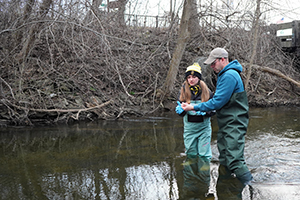 A citizen science volunteer learns the eDNA sampling protocol on Paint Creek.
