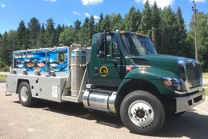 a side view of a Michigan DNR fish-stocking truck, with pine trees in the background