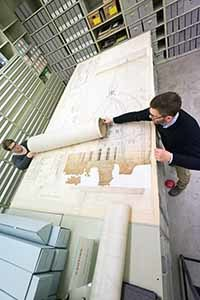 State Archivist Mark Harvey and archivist Andrea Gietzen pull several of the original architectural drawings of the state's capitol for scanning.