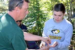 Historian Barry James hands a piece of pottery to a student on an archaeological dig in the Upper Peninsula.