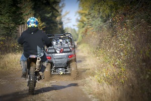 A view from behind of off-road vehicles riding away down a dirt trail, lined with mature trees