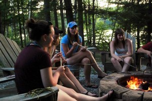 Three Youth Conservation Council members sit around a fire close to dusk.