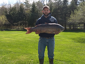 Angler Tyler Fisher holds up the state record bigmouth buffalo he caught