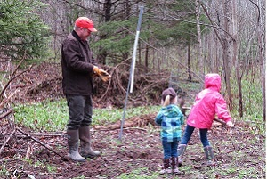 A man watches two small children as they walk through the woods