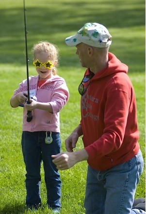 little girl wearing sunglasses, holding a fishing pole, while and older man helps her