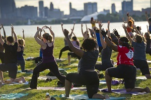 a group of people in summer exercise gear, doing yoga on Belle Isle
