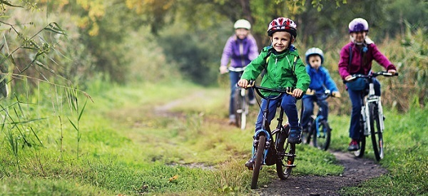 three kids wearing jackets and helmets, riding bikes on a trail toward you, followed by mom in the background