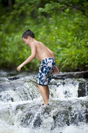 A young boy in a bathing suit balances amid the rushing water at Ocqueoc Falls, greenery in the background