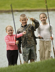 boy and two girls holding fishing poles and fish