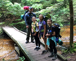 three young ladies and man hiking with backpacks on bridge over stream