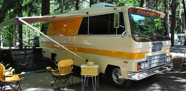 side to front view of a vintage camper, with the canopy up and camp chairs surrounding it