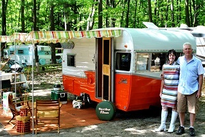 A woman and man stand in front of a colorful vintage camper, with other campers in the wooded background